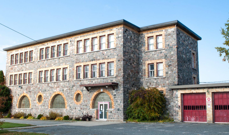 école datant de 1945 construite en pierre avec fenêtres rondes en demi-cercle situé au Témiscamingue à Laverlochère-Angliers, secteur Angliers